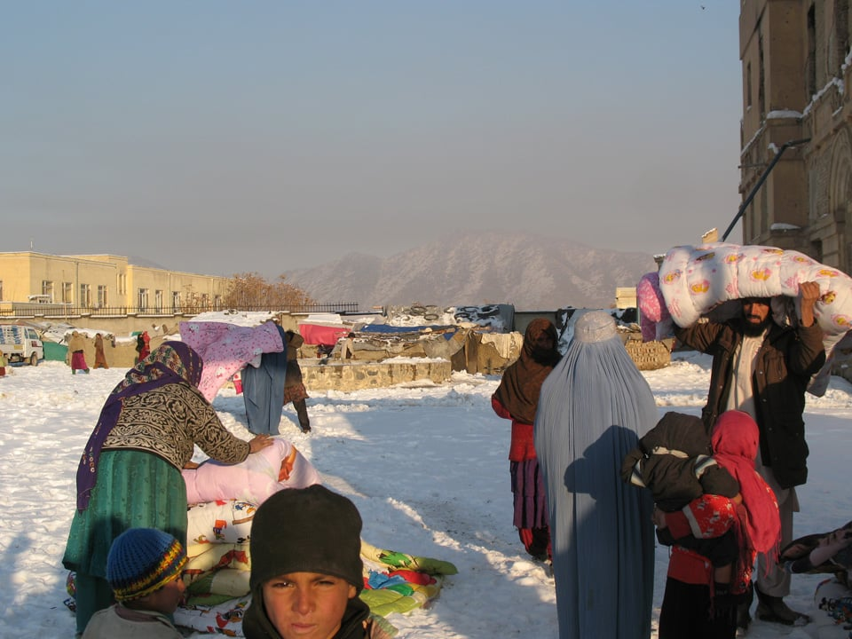 Afghan Peace Volunteers deliver duvets to women at the Darulaman refugee camp in Kabul.