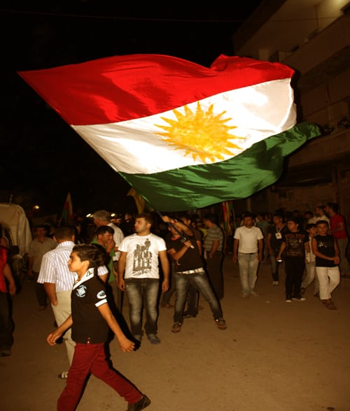 A protestor in central Qamishlou waves the flag of the autonomous Kurdistan Region of Iraq