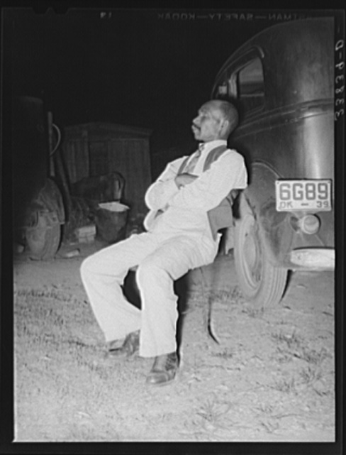 Russell Lee, Negro Sitting in Chair Which Is Leaning against Car Listening to the Speaker at Workers' Alliance Meeting, Muskogee, Oklahoma July 1939