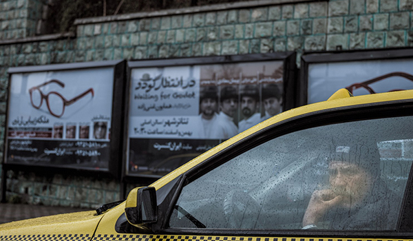 A taxi driver in his car on a rainy day in Iran