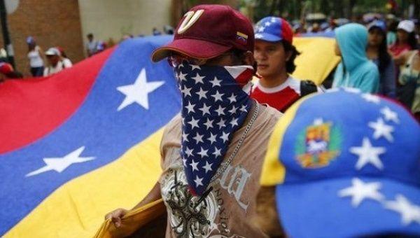 A Venezuelan opposition protester wears a U.S. flag bandanna around his face.