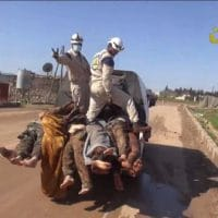 White Helmets workers posing with the bodies of dead Syrian soldiers