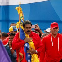 "Venezuelan President Nicolas Maduro holds the Venezuelan flag next to singer ""El Potro Alvarez"" during a rally in Caracas on Thursday"