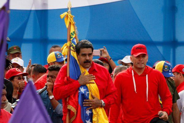 "Venezuelan President Nicolas Maduro holds the Venezuelan flag next to singer ""El Potro Alvarez"" during a rally in Caracas on Thursday"