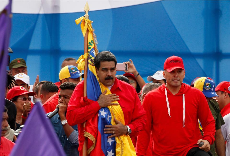 | Venezuelan President Nicolas Maduro holds the Venezuelan flag next to singer El Potro Alvarez during a rally in Caracas on Thursday | MR Online