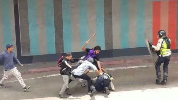 Opposition protesters gang up on and beat police officers. Telesur