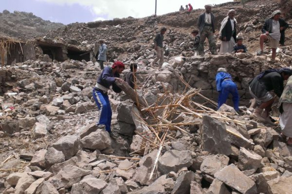 Villagers scour rubble for belongings scattered during the bombing of Hajar Aukaish