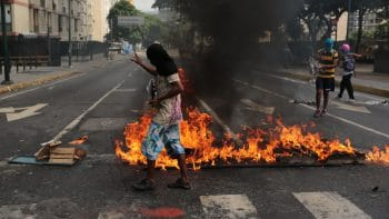 Anti-government protesters oversee a burning barricade in Caracas, Venezuela, Monday, June 26, 2017. Protesters have flooded the streets of Venezuela for months, demanding new elections and faulting President Nicolas Maduro's leadership for the country's triple-digit inflation, surging crime rates, and dire shortages of food and medicine. (AP Photo/Fernando Llano)