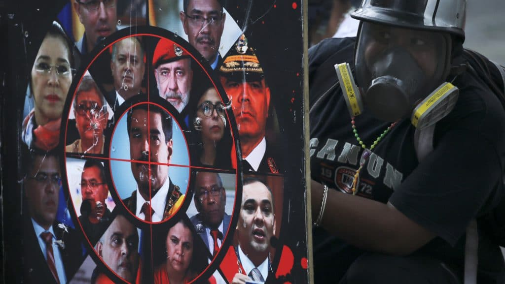 An anti-government protester holds a homemade shield brandished with photos of President Nicolas Maduro, government officials and a gun sight, during clashes with security forces blocking a march to the Supreme Court, in Caracas, Venezuela, Saturday, July 22, 2017. Protesters rallied Saturday in the Venezuelan capital for a march toward the embattled nation's Supreme Court, opposing Maduro's plan to rewrite the constitution. (AP Photo/Fernando Llano)