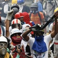 An opposition protester wields a shotgun an anti-government protest in Caracas, Venezuela, May 8, 2017. (AP/Ariana Cubillos)