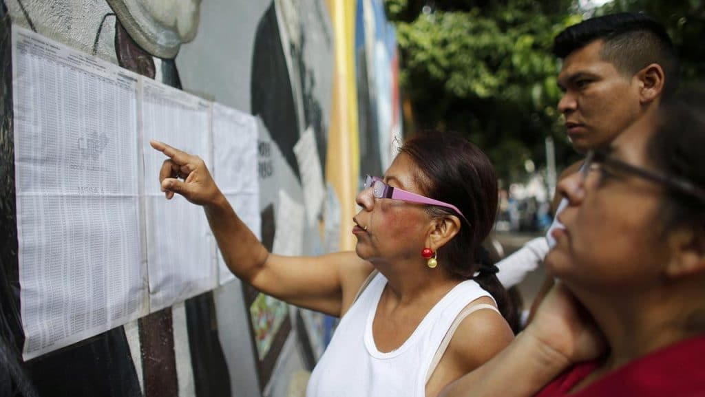 People check their voting machine at a list of voters provided by Venezuelan National Electoral Council, CNE, outside of a poll station during the election for a constitutional assembly in Caracas, Venezuela, July 30, 2017. (AP/Ariana Cubillos)