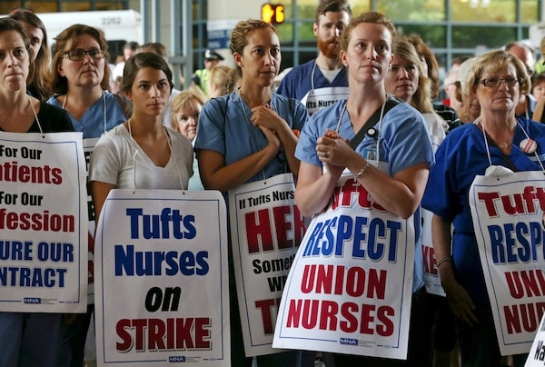 Nurses and supporters listen to speakers during the nurses strike outside Tufts Medical Center, Wednesday, July 12, 2017. Staff photo by Angela Rowlings.