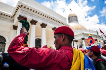 A man holds a Chávez action figure in front of the Legislative Palace