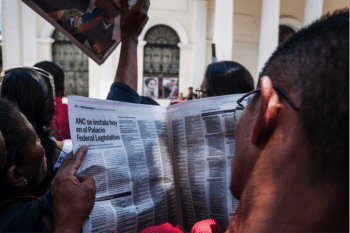 A man reads news about the Constituent Assembly in front of the Legislative Palace