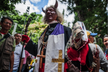 A man disguised as the devil representing evil among members from the Catholic church walks around Bolivar Square waiting for Constituent Assembly's installation