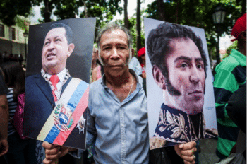 A man in Bolívar Square with Simón Bolívar and Chávez' portraits and a copy of 99's Venezuelan Constitution