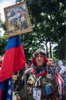 A man gathers around Bolívar Square with Simón Bolívar and Chávez' portraits and a copy of 99's Venezuelan Constitution