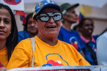 A woman wears Chávez` eyes themed sunglasses while waiting for the Constituent Assembly installation