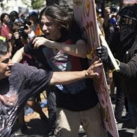 Anti-fascists push back against a fascist protestor with a Pinochet T-shirt