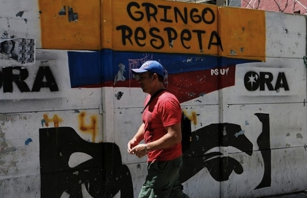 A man walks past a graffiti in Caracas, Venezuela August 13, 2017.