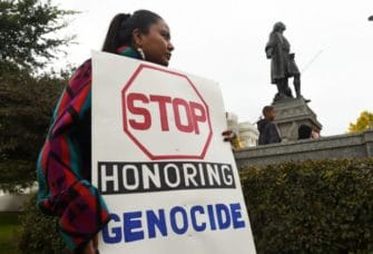 Woman holding sign protesting Columbus Statue