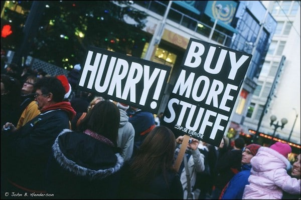 """Hurry! Buy More Stuff!"" sign at protest."