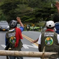 Two men waving at police car. Photo Credit: Juan Pablo Rueda Bustamante / El Tiempo