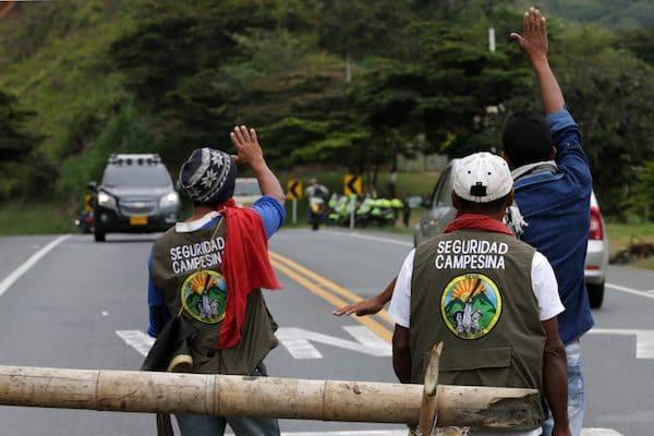 Two men waving at police car. Photo Credit: Juan Pablo Rueda Bustamante / El Tiempo