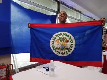 "Garfield Murrillo of the Belize-Venezuela Solidarity Committee holds the Belizean flag during ""Sundays with Maduro"" (Jeanette Charles/Venezuelanalysis)"
