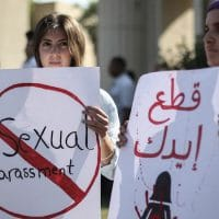 Ladies holding signs against sexual harassment.