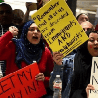 Dozens of pro-immigration demonstrators cheer and hold signs as international passengers arrive at Dulles International Airport. | Photo: Reuters