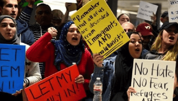 | Dozens of proimmigration demonstrators cheer and hold signs as international passengers arrive at Dulles International Airport | Photo Reuters | MR Online