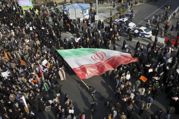 A demonstrator waves a huge Iranian flag during a pro-government rally