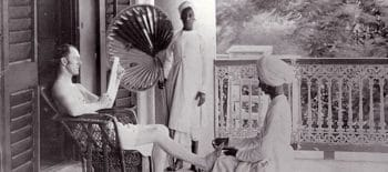 A British officer in India receives a pedicure from an Indian servant.