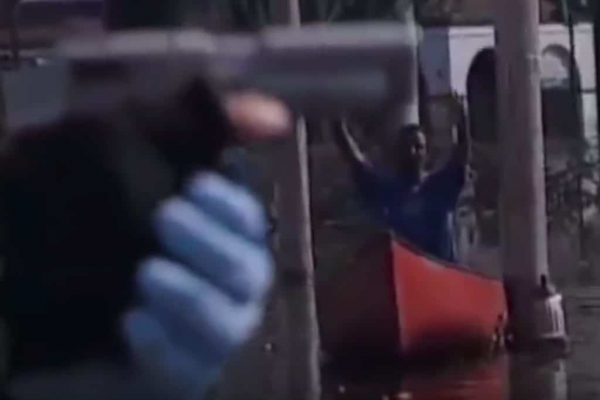 Person pointing a gun at someone drifting in a canoe after a natural disaster