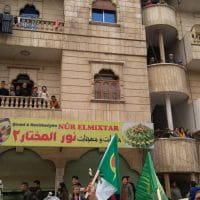 Refugees watching womens demonstration be from their balconies