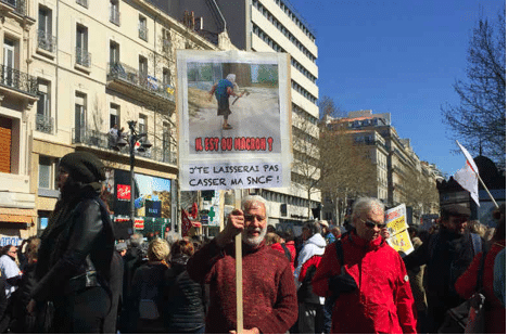 'Where is he that Macron? I won't let you break my SNCF [public rail service],' reads a placard with an axe-wielding citizen depicted at March 22 protest over cuts, labour rights and privatisation. Photo: Twitter/@mafalda1722