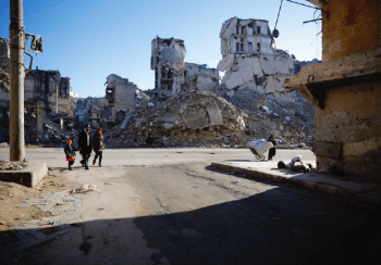 Family walking by ruins of buildings and homes.