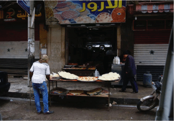 Man making bread and other goods outside of market.