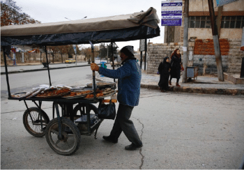 Man pushing cart of food.