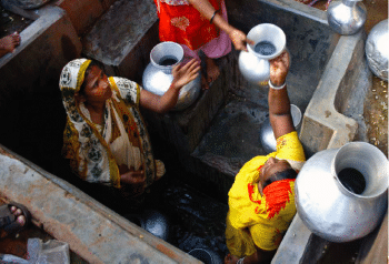 People fill water vessels at a well in India