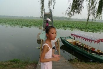 Lotus lake and Chinese girl – ecological paradise (photo by Andre Vltchek)