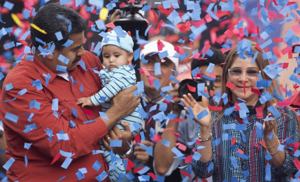 Venezuela's President Nicolas Maduro holds a baby as first lady Cilia Flores (right) applauds during a campaign rally in the parish of Catia in Caracas, Venezuela, last Friday