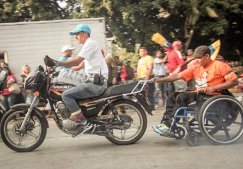 Man on motorcycle taking a man in wheelchair for a ride (PHOTO: Rafael Stédile)