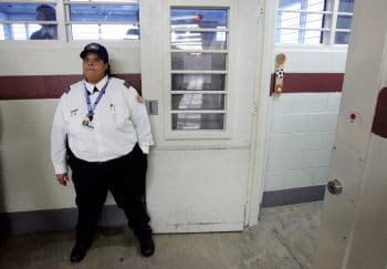 A guard holds open a door during a media tour