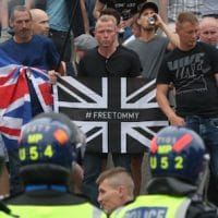 Police watch supporters of Tommy Robinson during their protest in Trafalgar Square, London yesterday calling for his release from prison