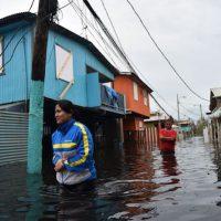 People walking through flooded waters (Photo: Hector Retamal/AFP/Getty Images.)