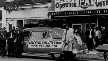 "A sign reading ""Last ride for Jim Crow"" in front of the headquarters of workers who pushed to overturn a discriminatory Kansas City ordinance by referendum. April 7, 1964. AP Photo"