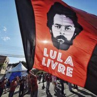 "In this July 8, 2018 file photo, a supporter of former Brazilian President Luiz Inacio Lula da Silva waves a banner decorated with an image depicting da Silva and message that reads in Portuguese: ""Free Lula,"" in front of the Federal Police Department where he is serving jail time, in Curitiba, Brazil. 