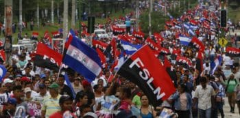 Sandinistas and followers of President Daniel Ortega wave their Sandinista flags in a march for peace, in Managua, Nicaragua, Saturday